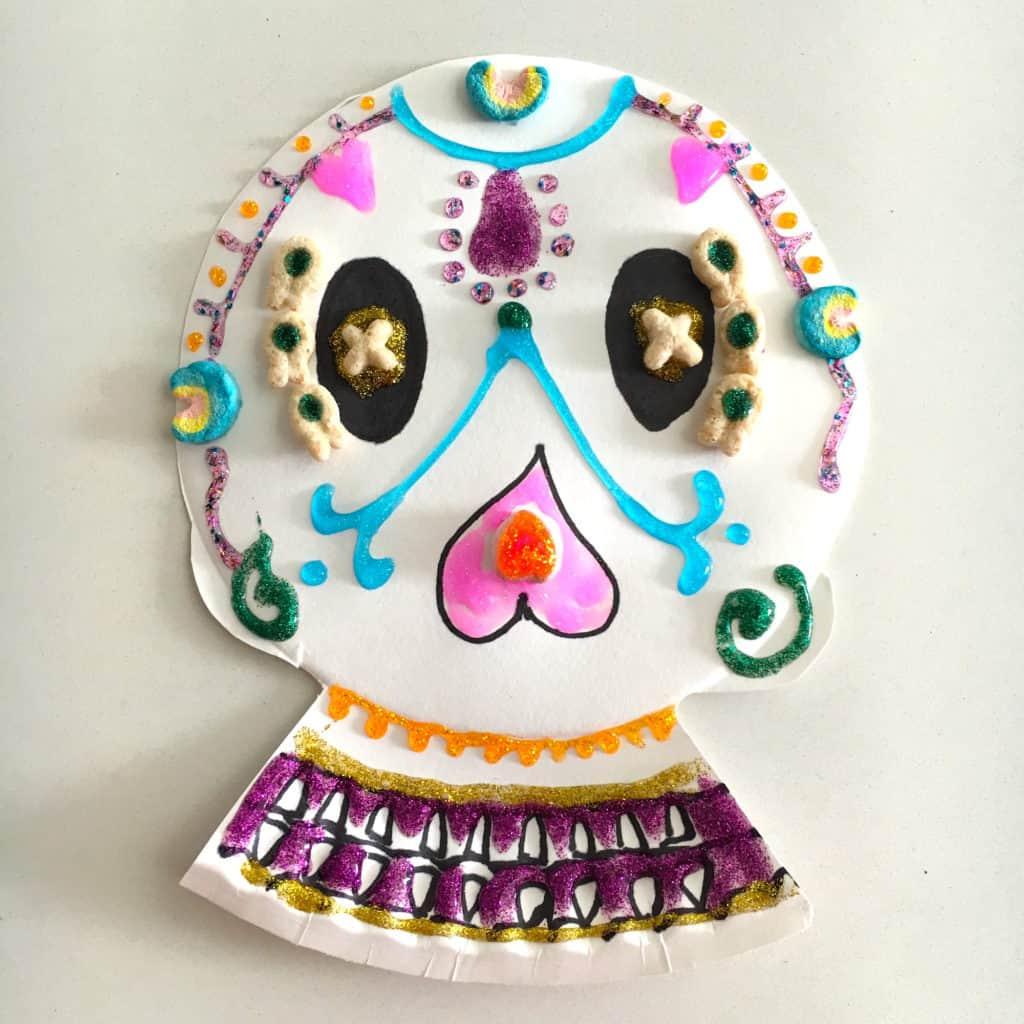Esta manualidad le encanta a los niños para honrar el día de los muertos. Haz tu propia calavera usando un plato de cartón, marcadores y cereal.