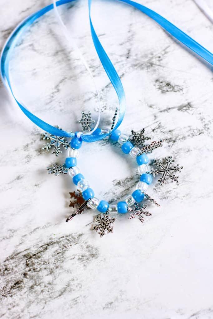 Cómo hacer una bella pulsera de cuentas y copos de nieve inspirada en la película Frozen, ideal para divertir a las princesas en casa.
