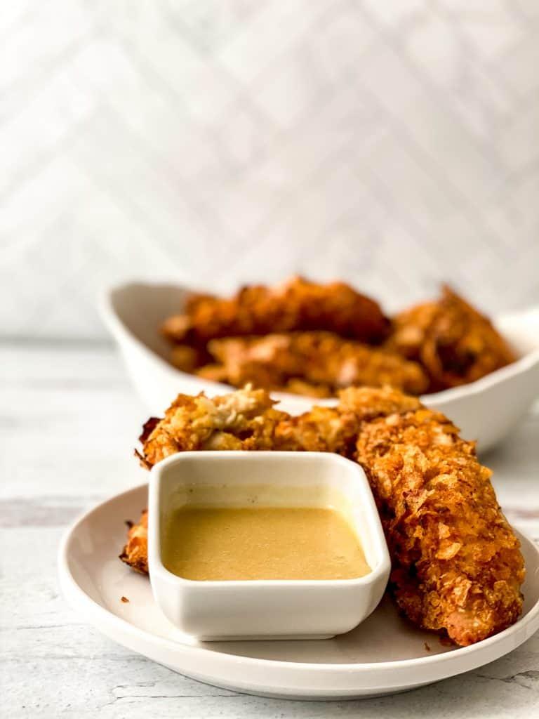 Estos deliciosos y crocantes nuggets caseros o tiras de pollo al horno les encantan a los niños y no necesitan freírse. ¡Se preparan en 20 minutos!